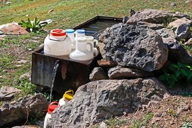 دبه هاي ماست و شیردامداران که قبل از شروع شستوشوی دام تهیه شده، در داخل چشمه نگهداری می کنند تا کار شستوشو به پایان برسد.