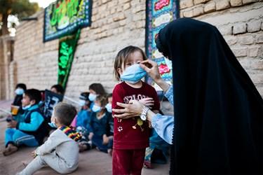 یکی از فعالین گروه جهادی حنیفا در حال زدن ماسک به یکی از کودکان