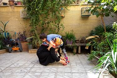 محمدمهدی با مادرش میترا نرگسی در حیاط منزلشان با پروتزهایی که به تازگی دریافت کرده است تمرین میکند.
