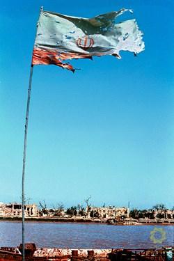 خرمشهر کوت شیخ/ 1361 در طول زمان اشغال شهر و زیر آتش درگیری دو طرف پرچم ایران در کنار رودکارون برافراشته مانده است
