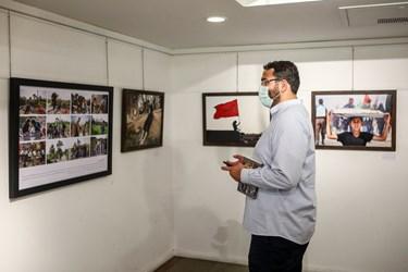 محمد مهدی دادمان در حال بازدید از نمایشگاه عکس «عطش وصل»