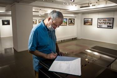 مرتضی سرهنگی نویسنده دفاع مقدس در حال نوشتن یادبود در نمایشگاه عکس «عطش وصل»