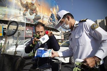 اهدای گل  و ماسک توسط پرسنل راهنمایی و رانندگی به موتورسوار همزمان با آغاز هفته نیروی انتظامی