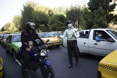 اهدای گل  و ماسک توسط مامور نیرویانتظامی به موتورسوار همزمان با آغاز هفته نیروی انتظامی