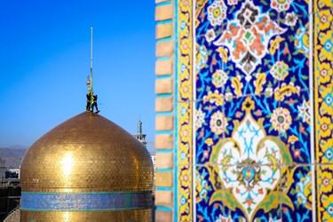 نصب کردن پرچم سبز گنبد ملکوتی حرم حضرت ثامن الحجج علیه السلام