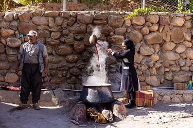 در روستای محمودآباد به روش سنتی و با احاق های هیزمی دانه های انار را می جوشانند.