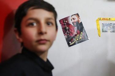 امیر رضا محمدی فرزند شهید امر به معروف محمد محمدی که دیوارهای  اتاق  خود را با عکسهای پدر آراسته است.