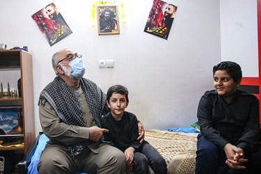 فرزندان شهید امر به معروف محمد محمدی که دیوارهای اتاق  خود را با عکسهای پدرشان آراسته اند به سردار نقدی نشان میدهند.