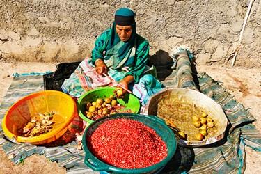 دانه کردن یکی از حوزه های کاری زنان روستاست که چوب دستی بر انارها می زنند تا دانه ها جدا شود.