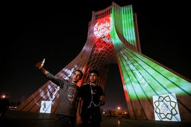 افغانستانی هایی که جهت تماشا و گرفتن عکس یادگاری از نورپردازی برج آزادی در میدان آزادی حاضر شده بودند.