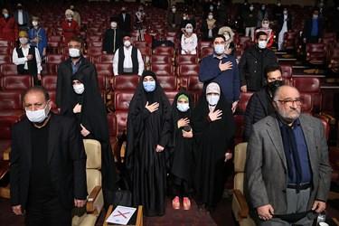 ادای احترام شرکت کنندگان در مراسم رونمایی از تندیس شهید سپهبد قاسم سلیمانی هنگام پخش سرود ملی در برج میلاد