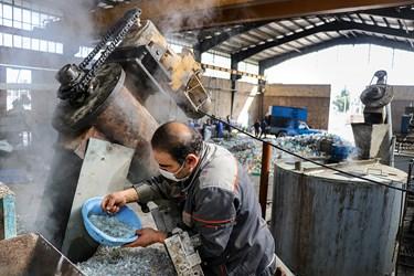کارگر در حال کنترل کیفیت پرک سفید شستشو شده  با آب گرم( دستگاه هات واش) است./کارگاه محراب