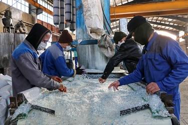 کارگرها در حال گرفتن ناخالصی های پرک سفید بر روی خط نوار چک هستند./کارگاه محراب