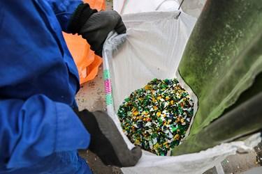 کارگر در حال خالی کردن پرک رنگی درون کیسه است./کارگاه محراب