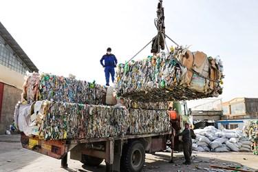 کارگرها در حال تخلیه ی بطری های پرس شده/کارگاه محراب