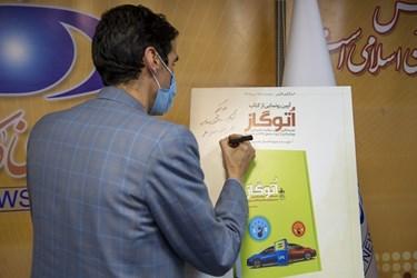 امضا مالک شریعتی سخنگوی کمیسیون انرژی در مجلس شورای اسلامی در آیین رونمایی از کتاب اتوگاز