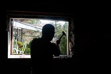 كارگران در حال تخريب ديوار و خارج كردن سالم پنجرههای رستوران ساحلی