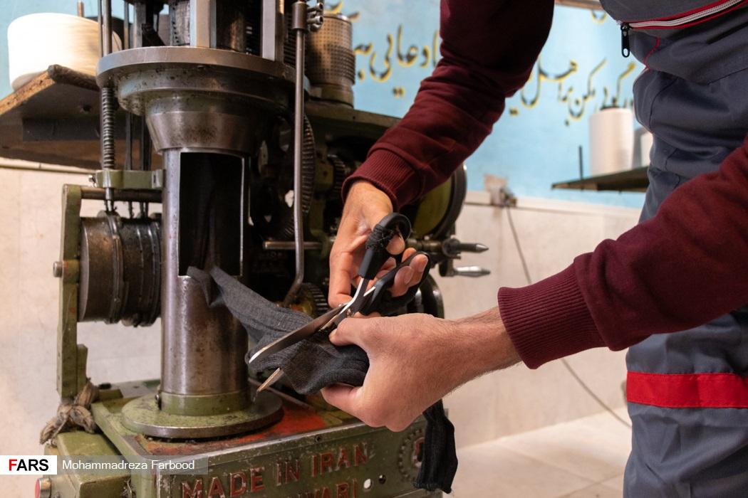بهبود یافته از اعتیاد در حال قیچی کردن جوراب بافته شده / کارگاه جوراب بافی و کشباف در مجموعه آموزش اشتغالزایی بهبود یافتگان از اعتیاد در شیراز