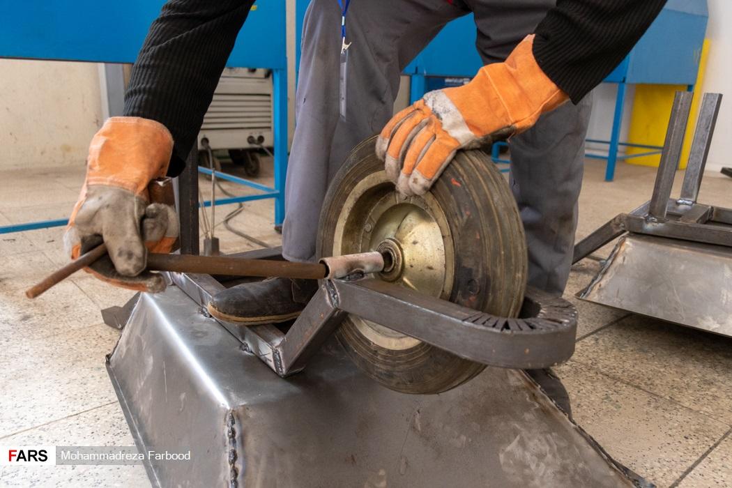 بهبود یافته از اعتیاد در حال بستن چرخ فرغون / کارگاه جوشکاری و تولید سازه های فلزی در مجموعه آموزش اشتغالزایی بهبود یافتگان از اعتیاد