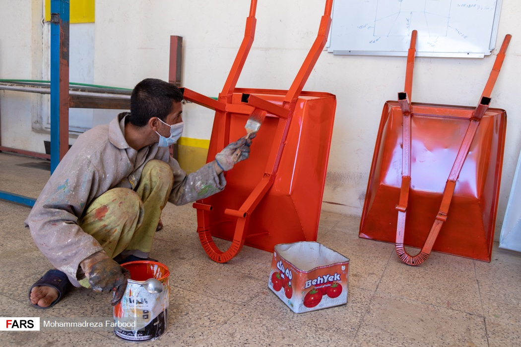 بهبود یافته از اعتیاد در حال رنگ کردن فرغون / کارگاه جوشکاری و تولید سازه های فلزی در مجموعه آموزش اشتغالزایی بهبود یافتگان از اعتیاد