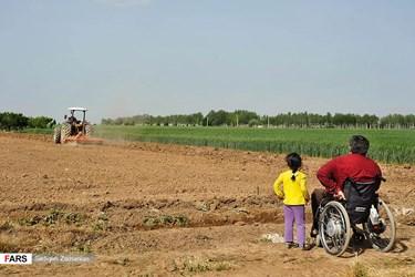 محمد مهین خاکی جانباز دفاع مقدس و دخترش، عسل در کنار زمین های کشاورزی که به تصمیم خود و به همراهی پدرش در آن مشغول به زراعت و دامداری است. او از روستای تپه قشلاق کرج در عملیات والفجر سال 66 بر اثر اصابت ترکش بمبهای عراقی از ناحیه کمر مجروح شد.