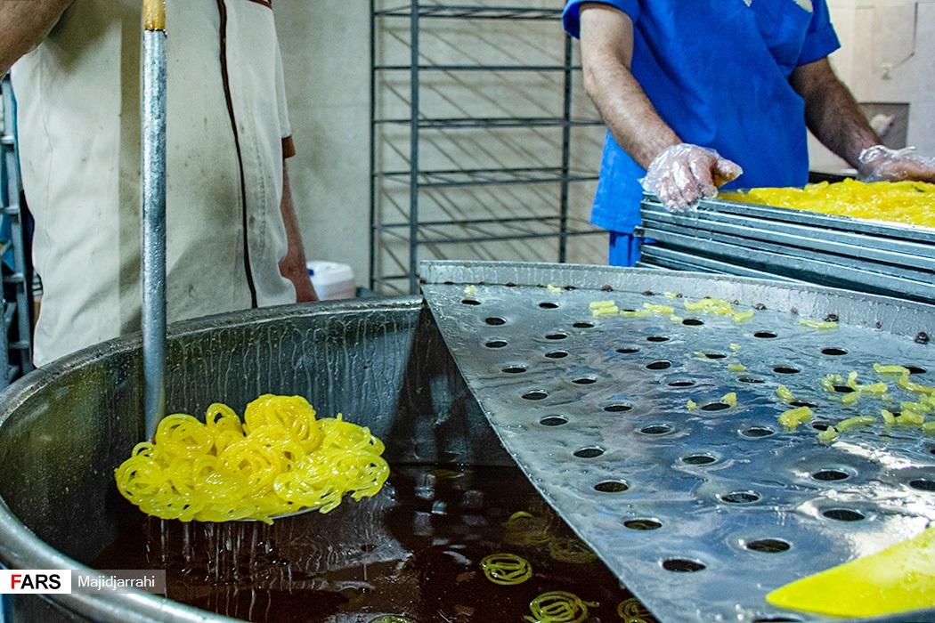خارج کردن زولبیایی پخته شده از دیگ شیره