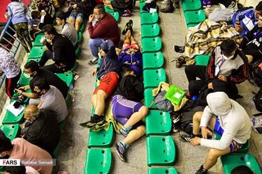 استراحت کشتی گیران در جایگاه تماشاگران در رقابتهای انتخابی تیم ملی کشتی فرنگی نوجوانان و جوانان یادواره شهدای دانشآموز استان کردستان در سالن آزادی سنندج