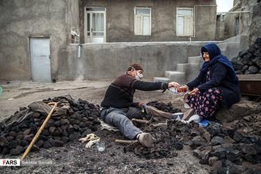 باجی خانم همسر آقای عبدی در حین کار از همسرش پذیرایی میکند. محمدنبی عبدی از ریشسفیدان روستای «قزلجهکند» شهرستان قروه؛ بیش از ۶۰ سال از عمرش را پای درست کردن سنگ پا گذاشته است. در این روستا با وجود ۵ معدن «پوکه» تولید «سنگ پا» رونق دارد.