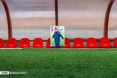 قاب عکس یادبود نادر دستنشان بر روی نیمکت در ورزشگاه شهید وطنی قائمشهر. نادر دست نشان متولد 1339 مربی مشهور فوتبال و مهمترین چهره فوتبالی قائمشهر بعد از درگیری با بیماری کرونا، در حالی از دنیا رفت که در یک هفته گذشته به مدد دستگاه زنده مانده بود.