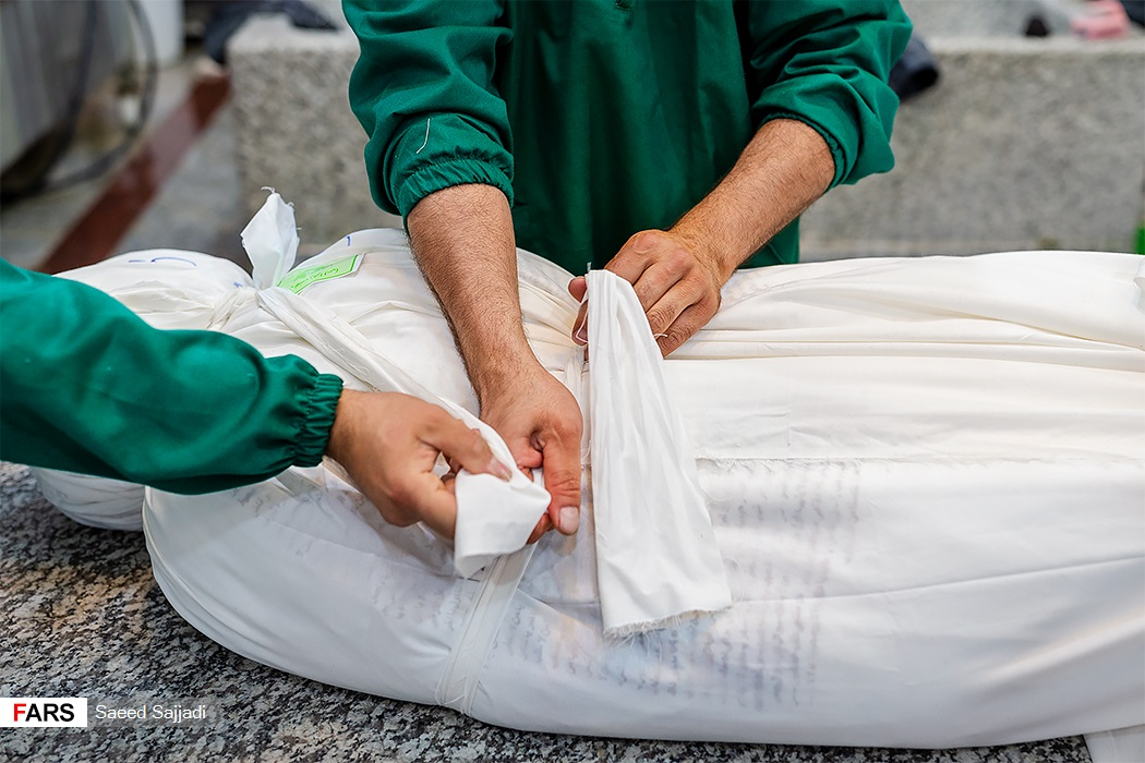 کارکنان سالن عروجیان بهشت زهرا(س)، میتها را کفن میکنند