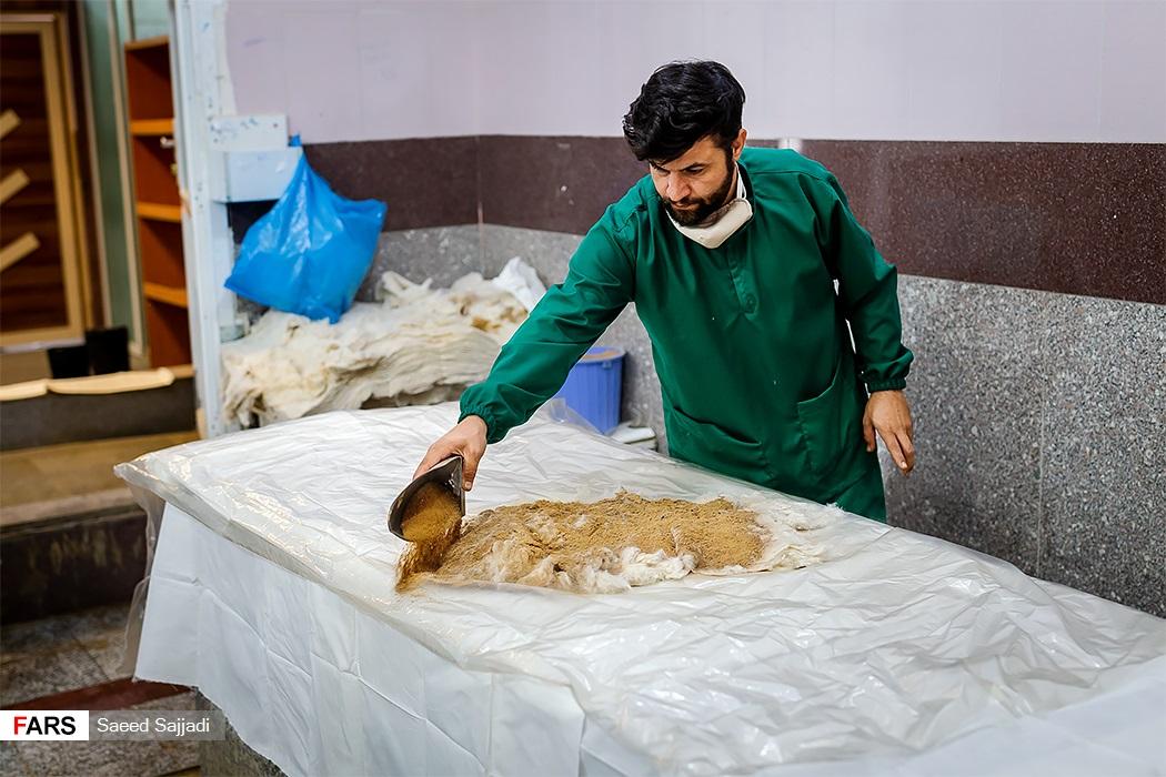 کارکنان سالن عروجیان بهشت زهرا(س) محل تکفین یکی از میتها را آماده میکند