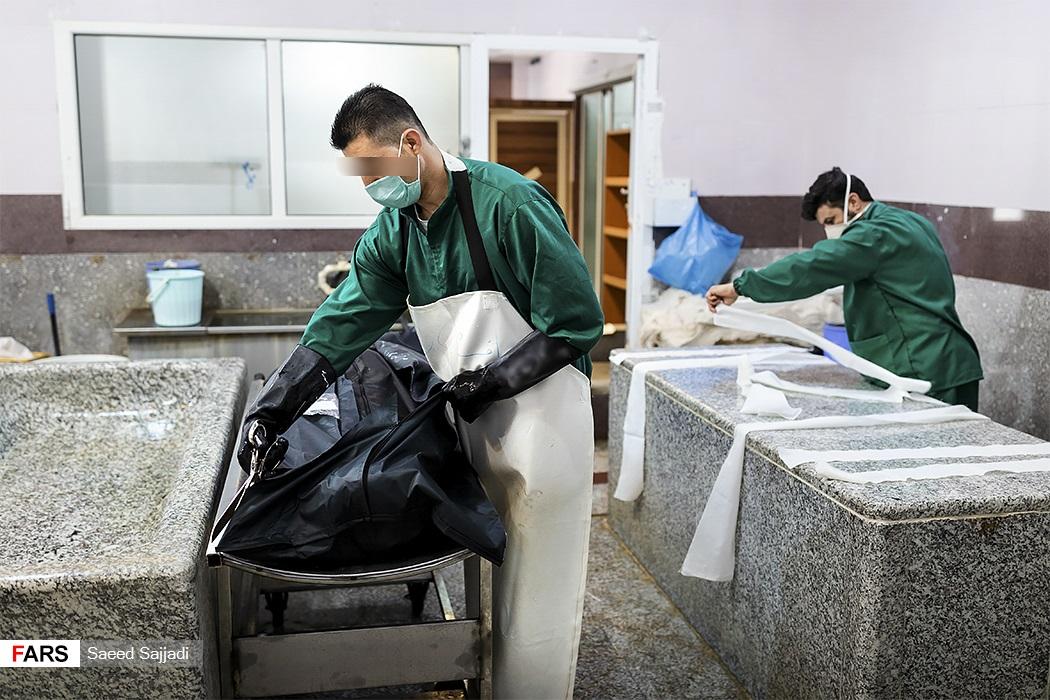 کارکنان سالن عروجیان بهشت زهرا(س)، یکی از میتها را آماده تغسیل میکند