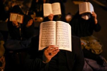قرآنهای به سر گرفته شده توسط شرکت کنندگان در مراسم احیای شب بیست و یکم ماه مبارک رمضان در خیابان ری تهران