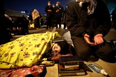 خانوادهای در مراسم قرآن به سرگرفتن  شب بیست و یکم ماه رمضان قرآنی را بر سر کودک به خواب رفته خود گذاشته است
