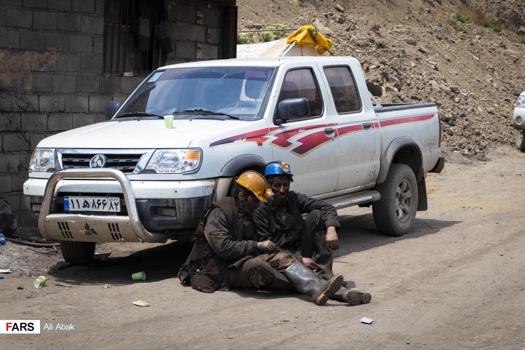 دو معدنچی پس از ساعتها تلاش بیفرجام در حال استراحت هستند