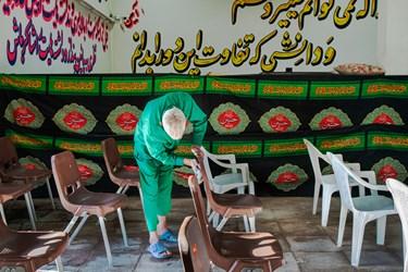 یکی از مددجویان در حال آماده سازی محل برگزاری محفل انس با قرآن است.