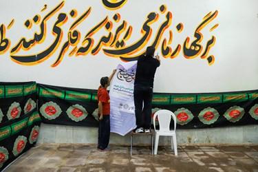 مددجویان در حال آماده سازی مکان برگزاری محفل انس با قرآن هستند.