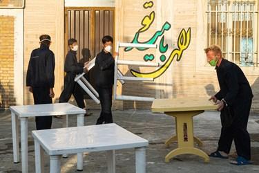 میزهای افطار در حیاط گرمخانه توسط مددجویان چیده می شود.