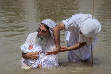 همزمان با خواندن آیهای یا بوثه از کتاب مقدس بر سر فرد مندایی آب ریخته میشود