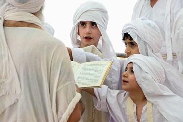 روحانی در حال خواندن بوثه(آیه ی ) ادرابشا برای تعمید دسته جمعی کودکان
