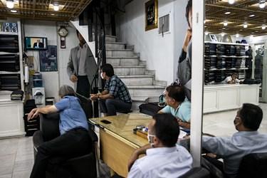تعدادی از فروشندگان پارچه کت شلواری مشغول تماشای دومین مناظره انتخاباتی 7 نامزد سیزدهمین دوره انتخابات ریاست جمهوری  هستند