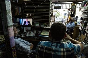 تعدادی از فروشندگان لوازم تحریر مشغول تماشای دومین مناظره انتخاباتی 7 نامزد سیزدهمین دوره انتخابات ریاست جمهوری هستند.