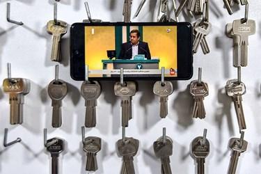 صاحب یک کلیدسازی در بجنورد با استفاده از تلفن همراه خود دومین مناظره انتخاباتی 7 نامزد سیزدهمین دوره انتخابات ریاست جمهوری را تماشا میکند.