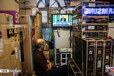 فروشنده لوازم صوت و تصویر در مشهد در حال تماشای دومین مناظره انتخاباتی 7 نامزد سیزدهمین دوره انتخابات ریاست جمهوری است.