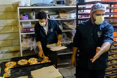 بسته بندی  پیتزاهای آماده شده توسط اعضای گروه جهادی پویش همسایه در سالروز میلاد امام رضا(ع) برای توزیع در میان خانوادههای نیازمند در جنوب استان تهران