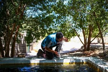 علی بعد از پایان کار خود از گرمای زیاد و طاقت فرسا کمی آب به صورت خود میزند.