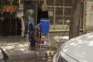 کسبه یزدی با قرار دادن مخزن آب جلوی مغازه به عابران آب خنک می دهند