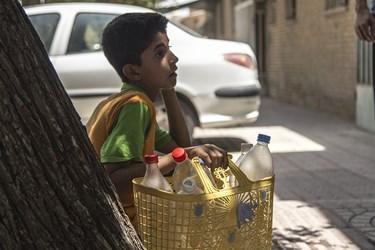 کودک یزدی در انتظار تامین آب زیر سایه درخت