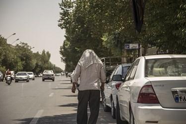 شهروند یزدی برای فرار از گرما سر خود را پوشانده است