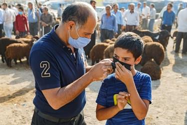 پدری در حال تلاش برای بستن بند پاره شده ماسک صورت پسرش است.